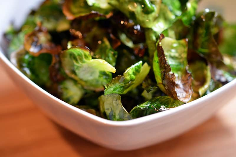 A bowl of crispy Brussels sprouts chips with browned edges