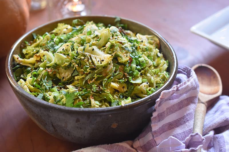 A closeup shot of a bowl filled with an Asian shaved brussels sprouts salad next to a wooden spoon and cloth napkin.