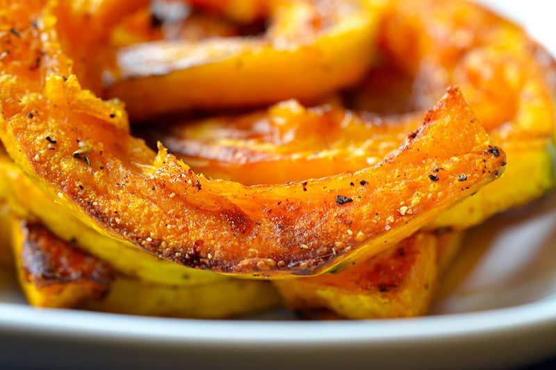 A closeup shot of wedges of roasted kabocha squash on a white plate.