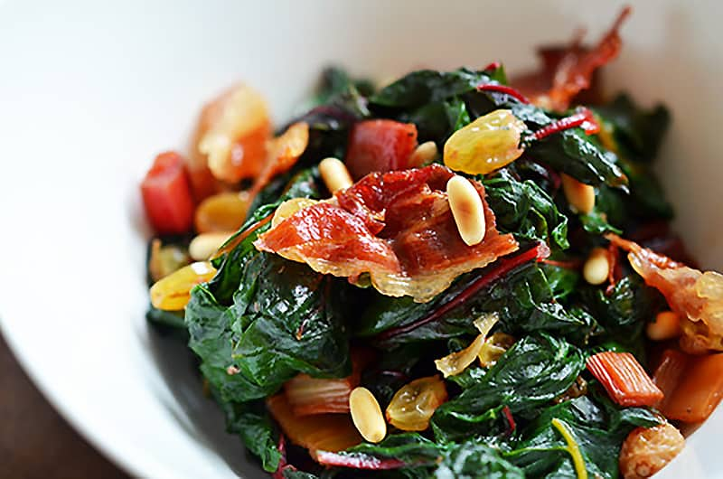 A shot of a white bowl filled with swiss chard, toasted pine nuts, raisins, and crispy prosciutto.