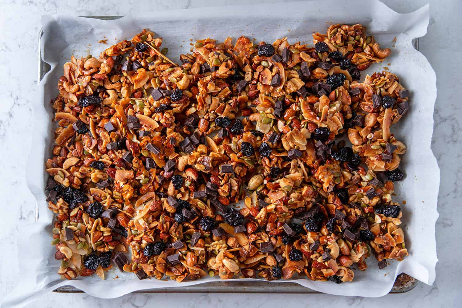 A tray of chocolate cherry paleo granola on a rimmed baking sheet lined with parchment paper