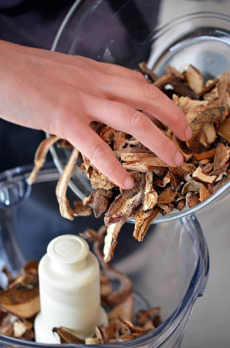 Adding a bow of dried porcini mushrooms to a food processor
