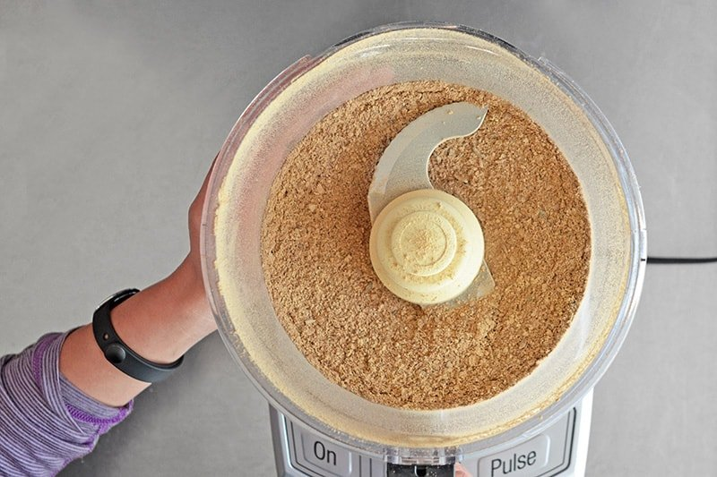 An overhead shot of powdered dried porcini mushrooms in an open food processor