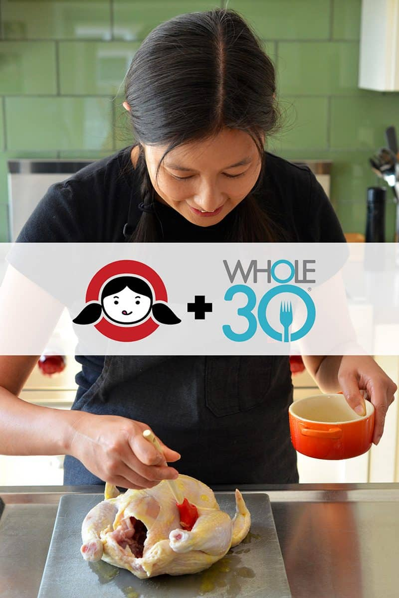 A brunette brushing ghee on a whole chicken. There is a banner that show the Nom Nom Paleo Logo + Whole30