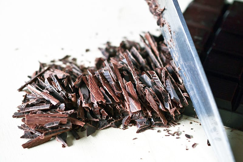 A closeup of thinly slicing a bar of dark chocolate with a chef's knife