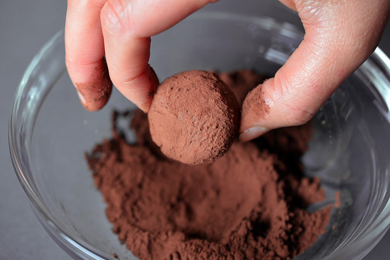 A Nom Nom Paleo Chocolate Truffle is dipped into a bowl of unsweetened cocoa powder