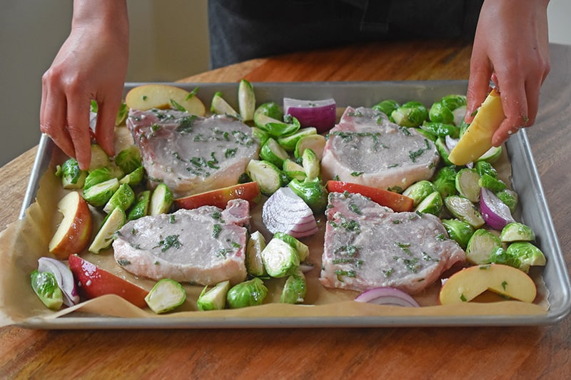 Arranging the ingredients for Sheet Pan Pork Chop Supper in a single layer on a rimmed baking sheet.