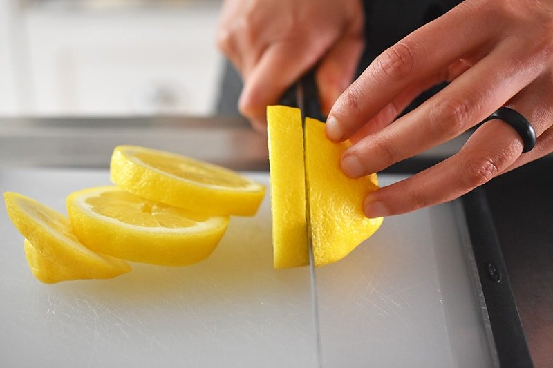 A closeup of slicing lemons into 1/2 inch slices.