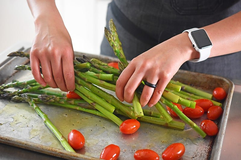 Tossing asparagus and grape tomatoes on a rimmed sheet pan with olive oil and seasoning.