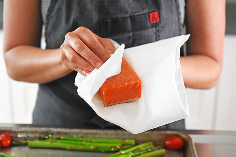 Patting a salmon fillet dry with a paper towel.