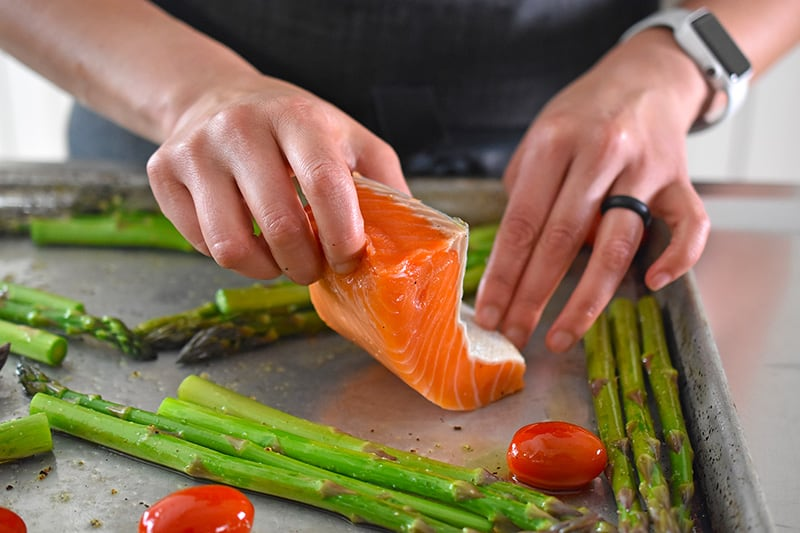 Placing a salmon fillet on a rimmed baking sheet for Sheet Pan Salmon Supper