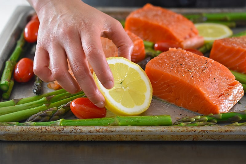 Adding lemon slices to the Sheet Pan Salmon Supper tray.