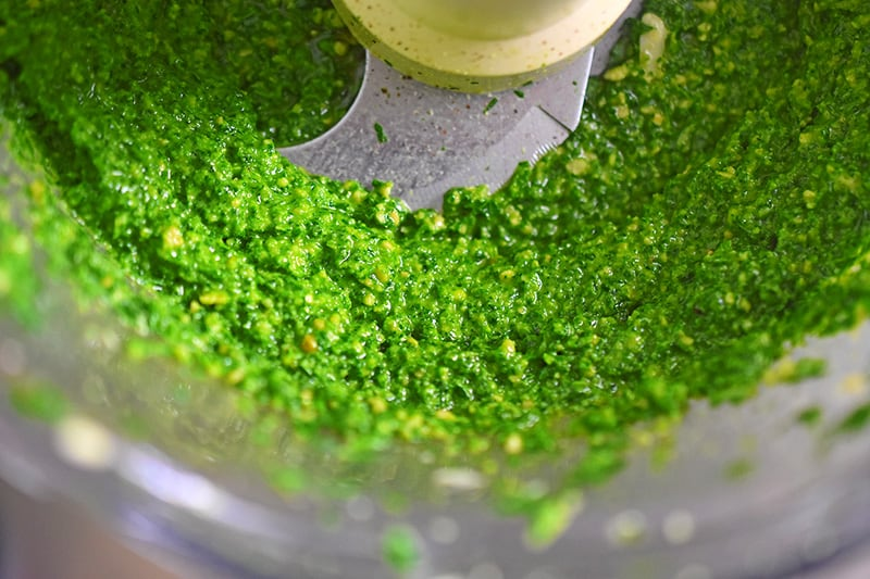 A closeup of Arugula pesto in a food processor.