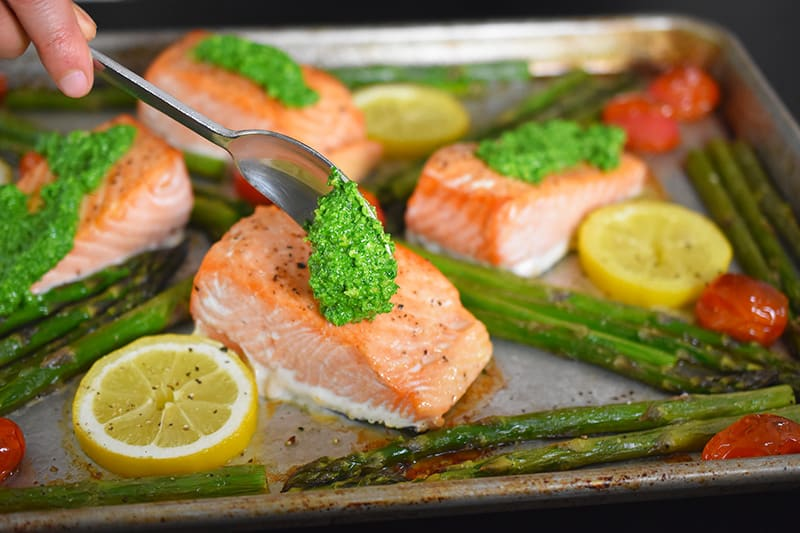 Adding a spoonful of arugula pesto on the fish in Sheet Pan Salmon Supper