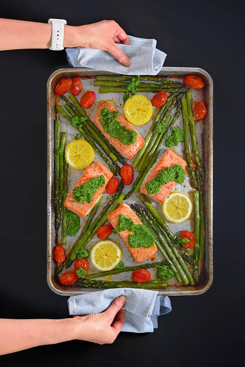 An overhead shot of someone holding a Sheet Pan Salmon Supper.