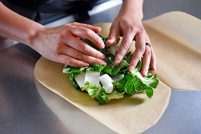 Someone assembling chopped and seasoned bok choy on the heart-shaped parchment paper for paper-wrapped chicken.