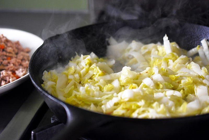 Sautéing sliced napa cabbage in a cast iron skillet.