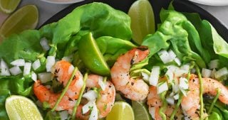 An overhead shot of Paleo Shrimp Tacos on a bed of lettuce. There is a bowl of Avocado Crema on the top left.
