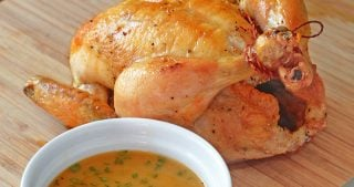 A closeup shot of Weeknight Roast Chicken on a wooden cutting board with gravy in a ramekin.