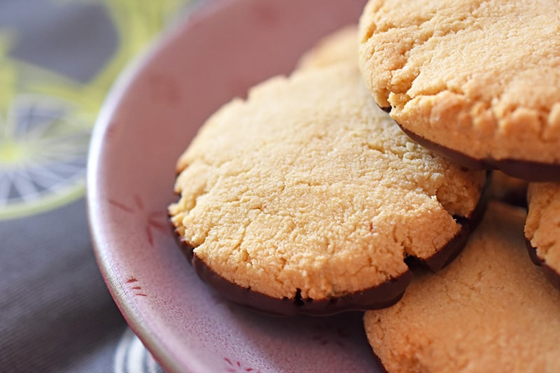 A closeup shot of paleo and vegan world's easiest cookies on a plate. The bottom of the cookies are dipped in chocolate.