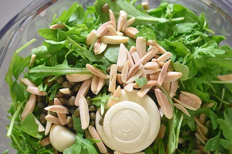 An overhead view of the ingredients for arugula pesto in a food processor.