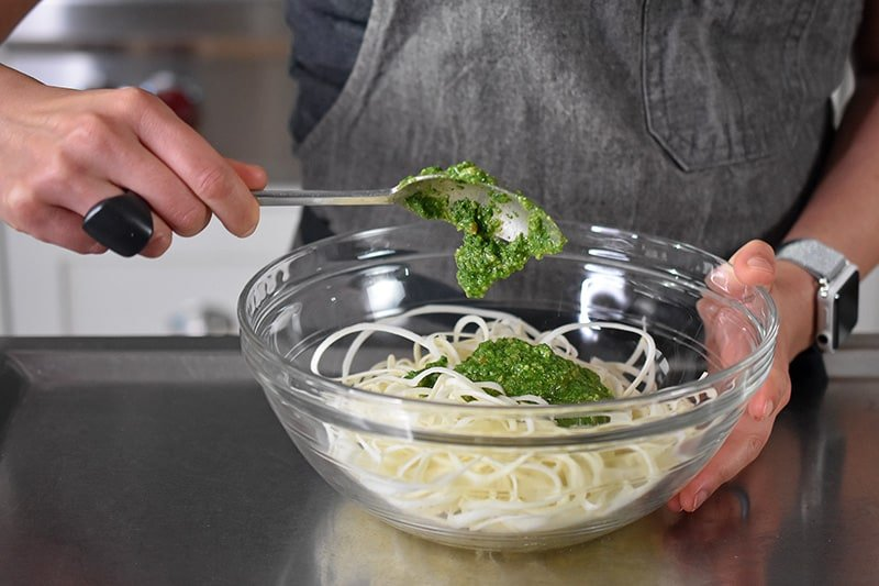 Someone adding a spoonful of paleo and Whole30 arugula pesto into a bowl of spiralized vegetables.