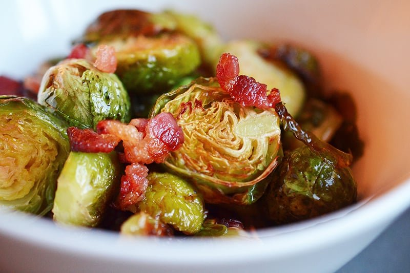 A side view of Roasted Brussels Sprouts and Bacon in a white bowl