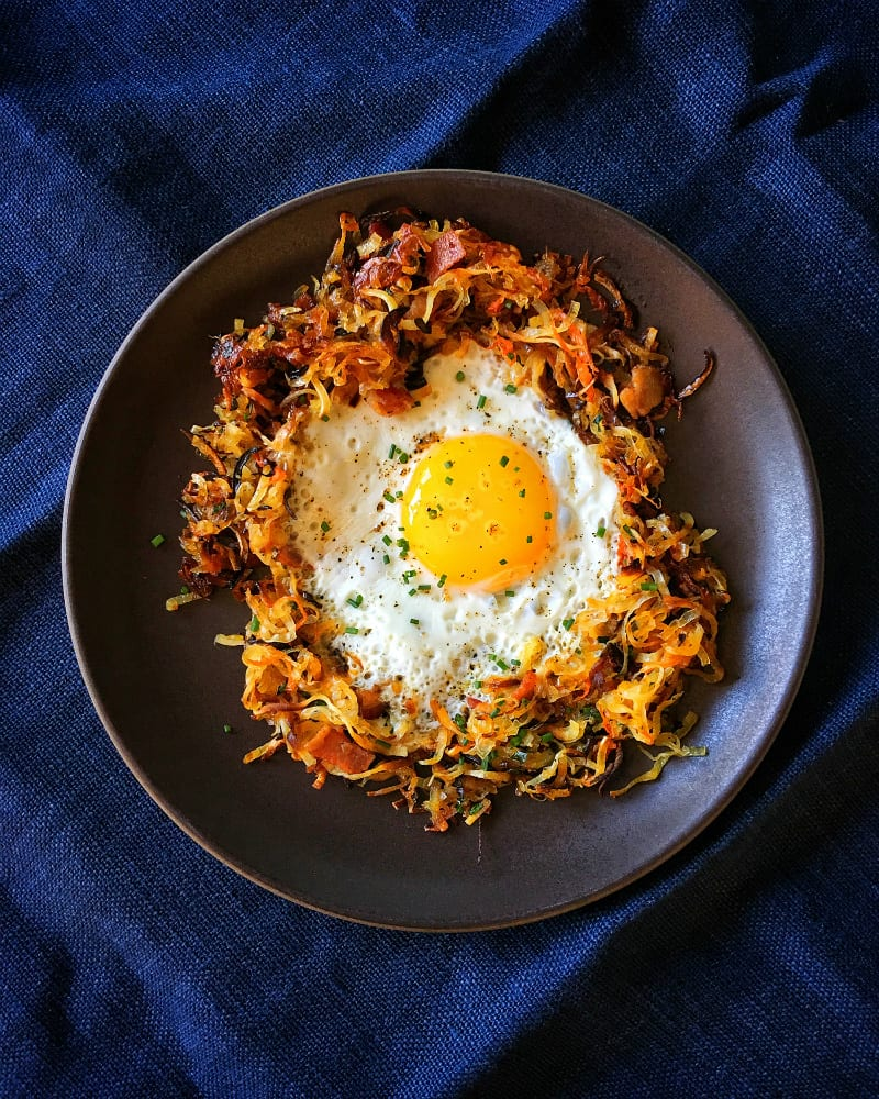 An overhead shot of a fried egg in a Crispy Swoodles with Bacon nest!