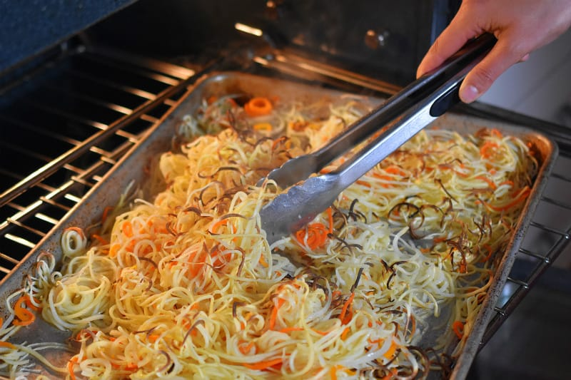 Crispy Swoodles being tossed by a pair of tongs as it cooks in the oven.