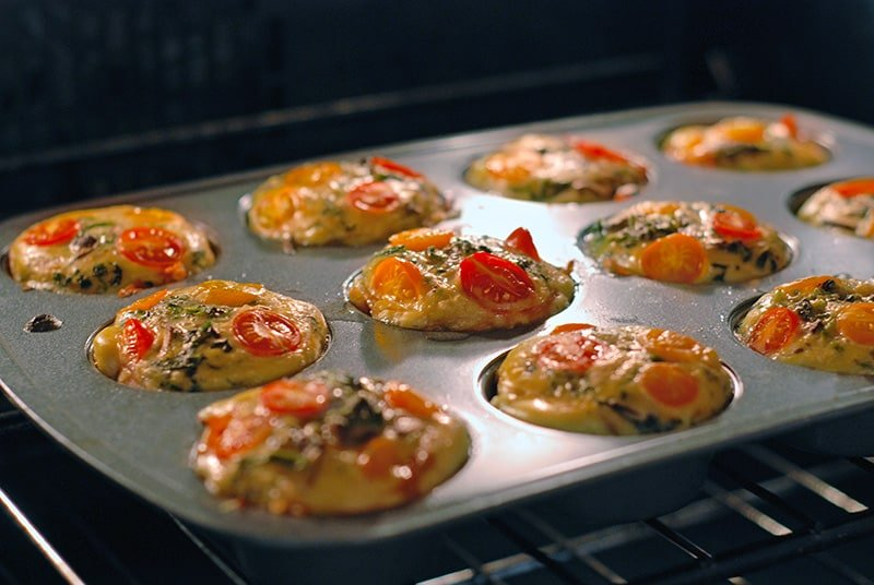 Prosciutto-Wrapped Mini Frittata Egg Muffins baking in the oven.