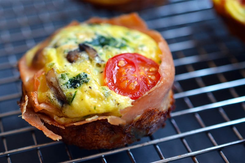 A closeup of a Prosciutto-Wrapped Mini Frittata Muffin on a wire rack