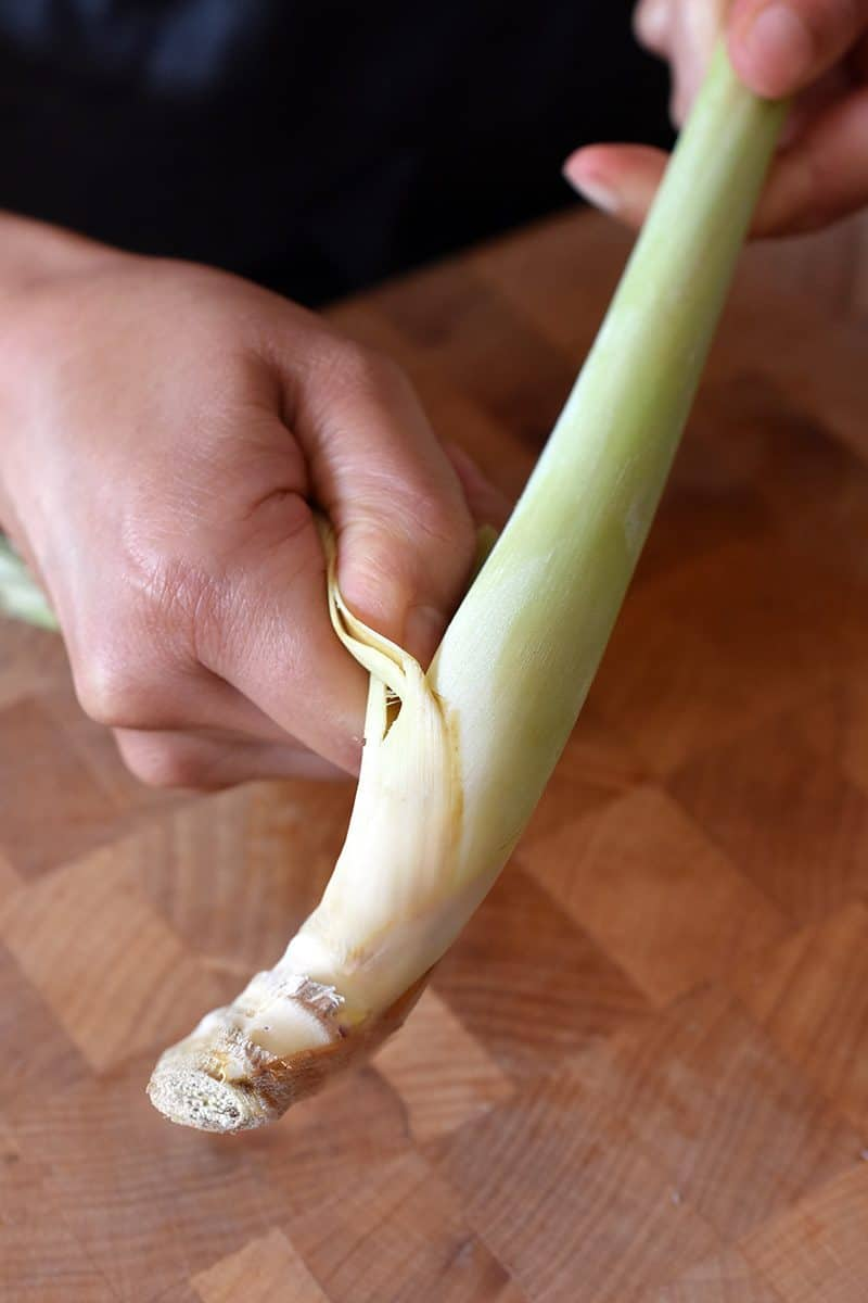 A person peeling off the tough outer leaves of a lemongrass stalk over a wooden cutting board