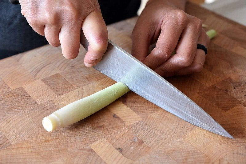 Cutting a trimmed lemongrass stalk so that it is the tender part near the base, about 3-4 inches from the root end.