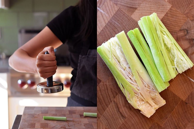 Smashing trimmed lemongrass stalks with a meat pounder