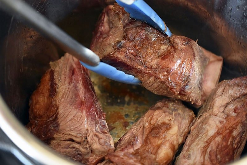 Searing the short ribs in batches in the Instant Pot