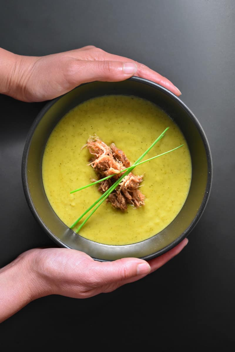 Someone holding a bowl of Instant Pot curried cream of broccoli soup topped with kalua pig.
