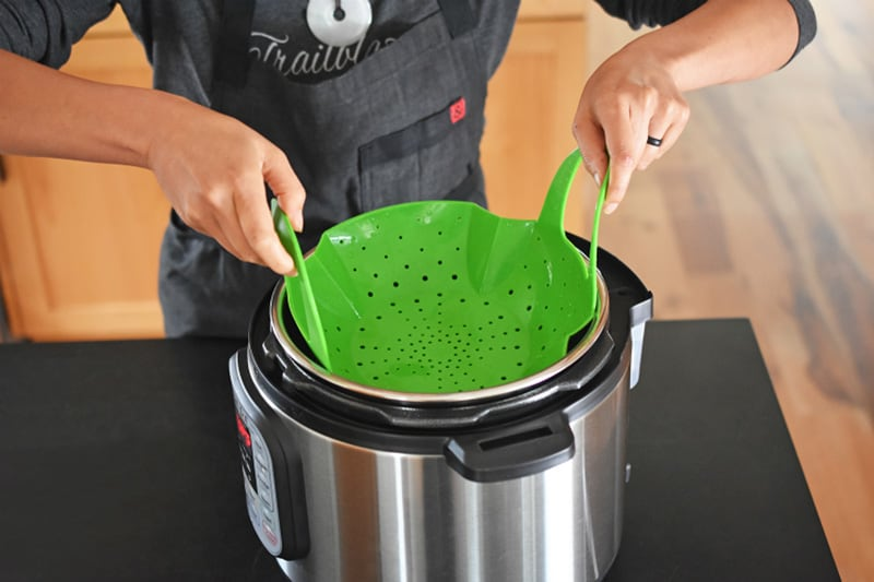 Someone is shown placing a green silicone steamer insert into an Instant Pot.