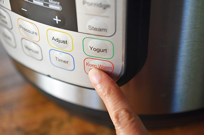 A finer is pressing the Keep Warm/Cancel button on an Instant Pot