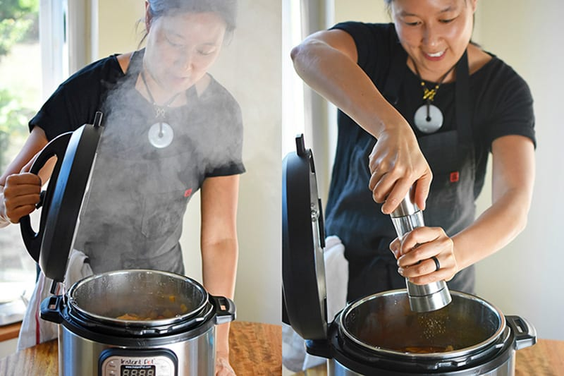 A woman is opens and Instant Pot with lots of steam coming out, and adds freshly cracked black pepper