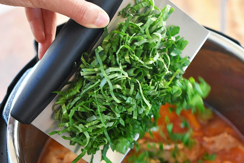 A hand is adding minced fresh herbs to the Instant Pot.