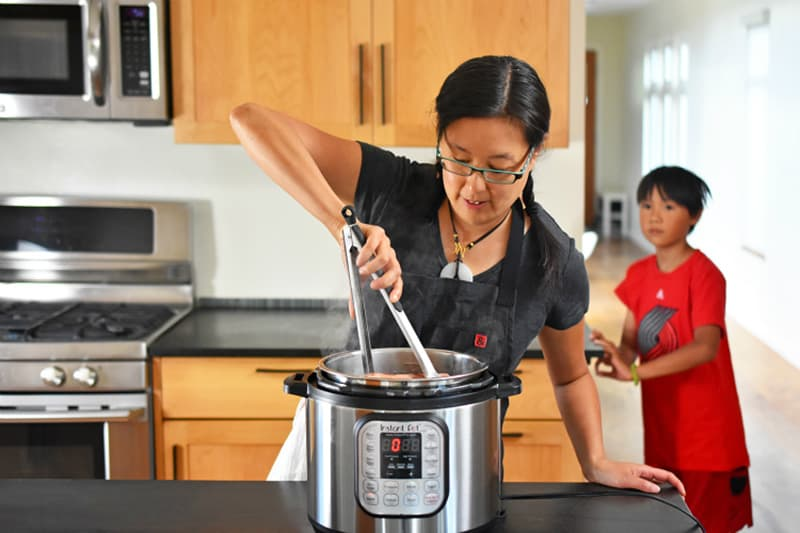 An Asian woman is using tongs to stir Instant Pot Summer Italian Chicken while a small boy watches.