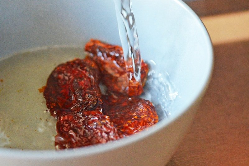 Water is poured into a bowl filled with sun-dried tomatoes.
