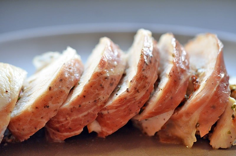 A side view of sliced Chicken Prosciutto Involtini on a platter