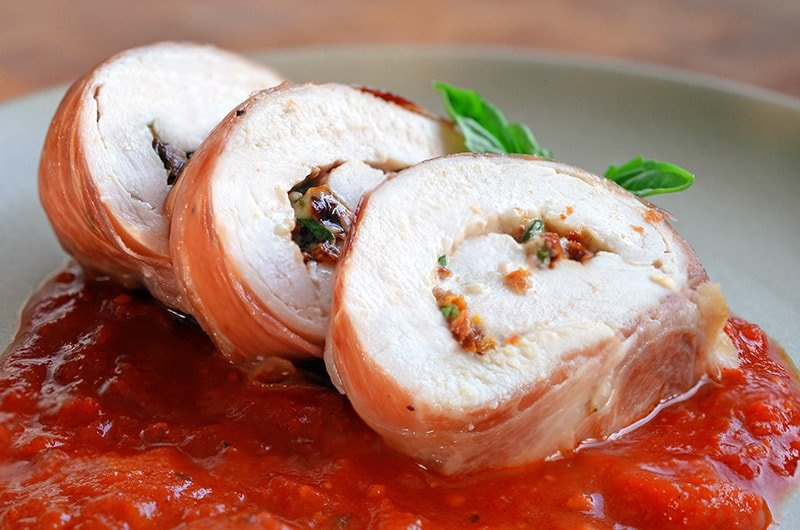 Sliced Chicken Prosciutto Involtini is resting on an angle on a bed of marinara sauce.