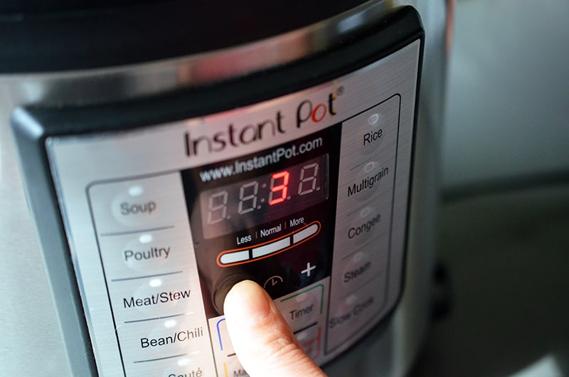 A person is programming the Insant Pot to cook under high pressure