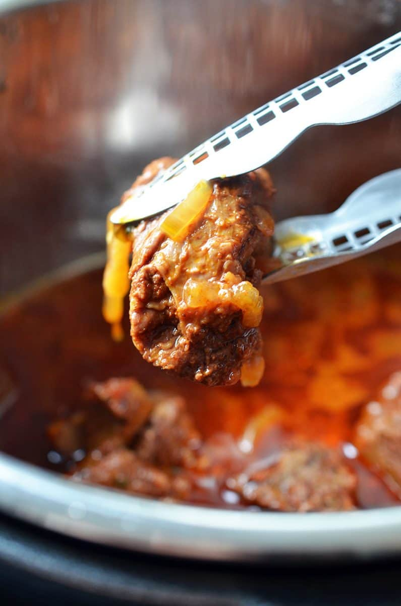 A pair of tongs has picked up a piece of Instant Pot Mexican Beef from the Instant Pot