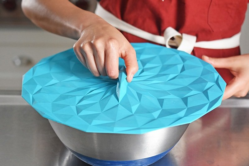 Someone covering a metal bowl with a silicone lid.