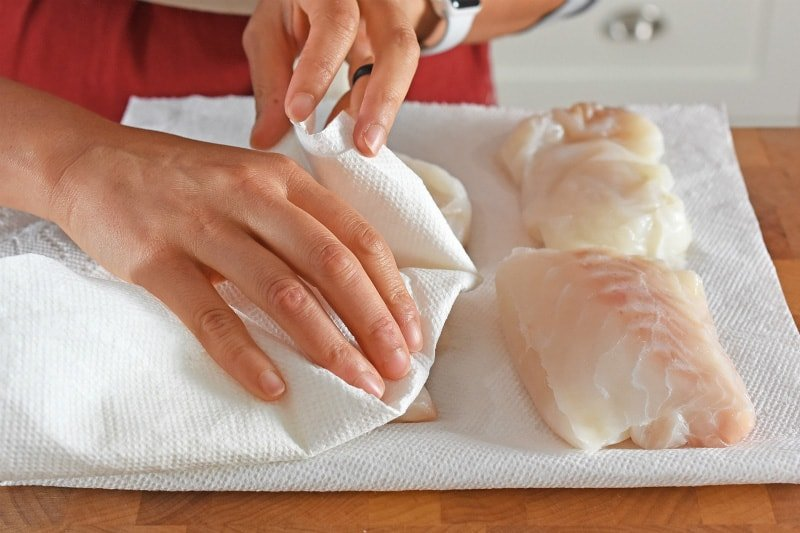 Boneless skinless cod fillets are patted dry between two pieces of paper towel.