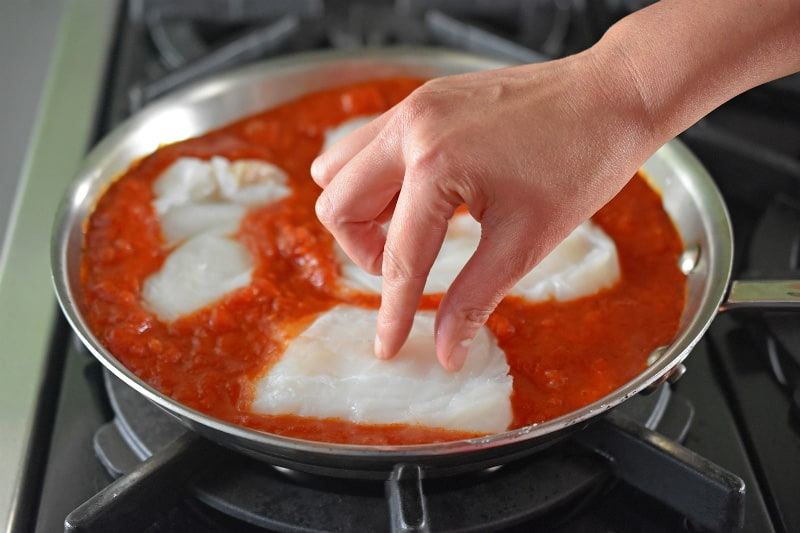 The seasoned cod fillets are carefully tucked into the simmering marinara sauce.