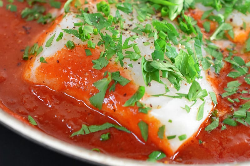 A closeup shot of Poached Cod in Tomato Sauce